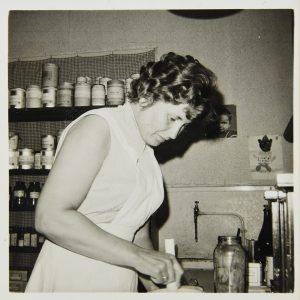 Zwartwit foto van Elly Heerschap aan het werk in de apotheek